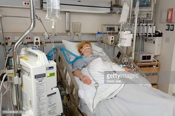 Mature female patient on respiratory ventilator in intensive care unit