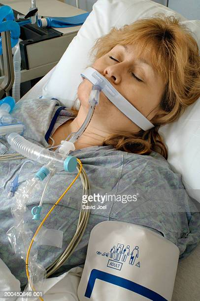 mature female patient on respiratory ventilator in intensive care unit - patient on ventilator stock pictures, royalty-free photos & images