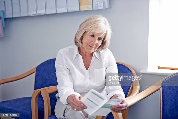 mature female patient reading leaflet in hospital waiting room - bulletin board flyer stock pictures, royalty-free photos & images