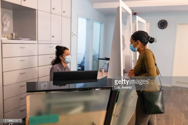 mature female patient walking to hospital receptionist - shoulder bag stock pictures, royalty-free photos & images