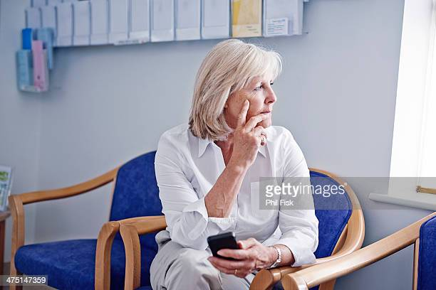 mature female patient with mobile phone in hospital waiting room - waiting stock pictures, royalty-free photos & images