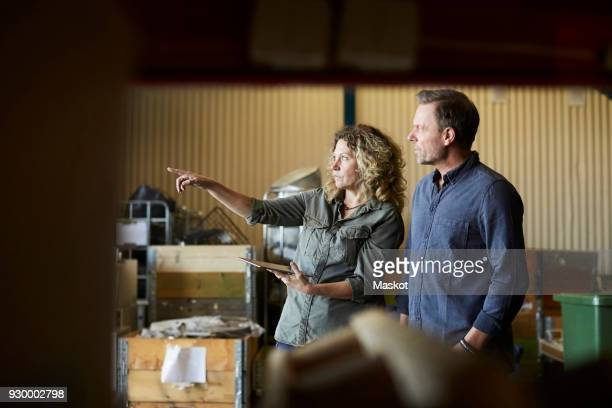 mature female pointing to male colleague while holding digital tablet at warehouse - contact list stock photos and pictures