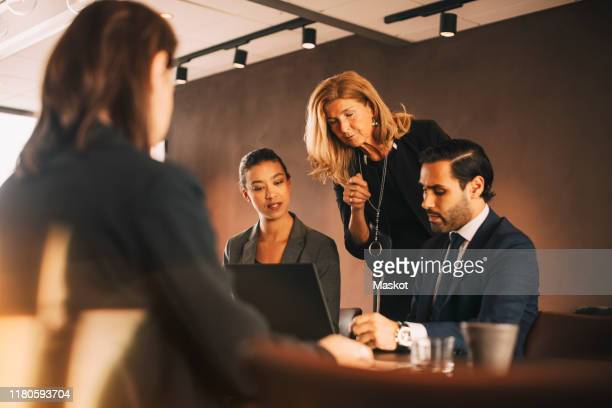 mature female professional discussing with lawyers at office - legal system stock pictures, royalty-free photos & images