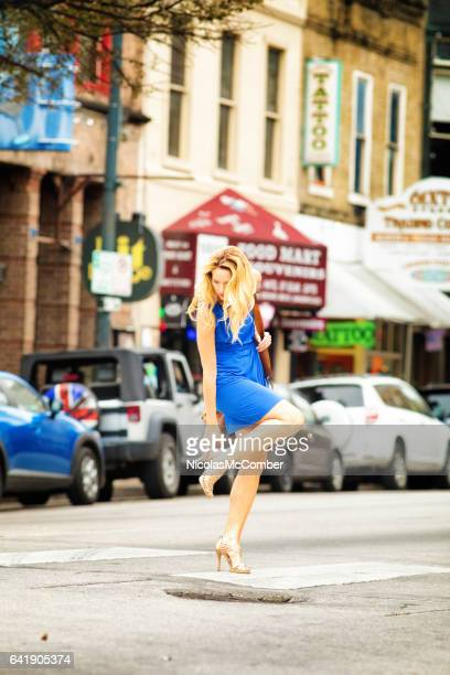 mature female readjusts her shoe while crossing the street - cocktail dress stock pictures, royalty-free photos & images