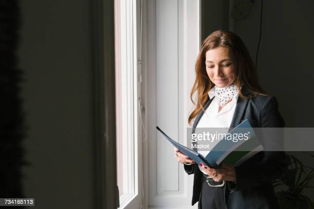 Mature female real estate agent reading brochure while standing by window at home