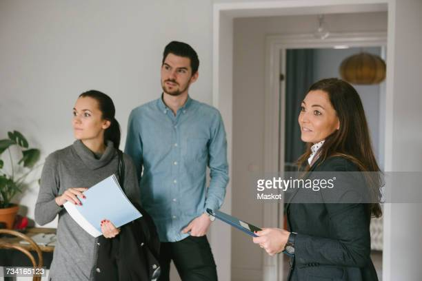 Mature female realtor standing with young couple holding brochures at home