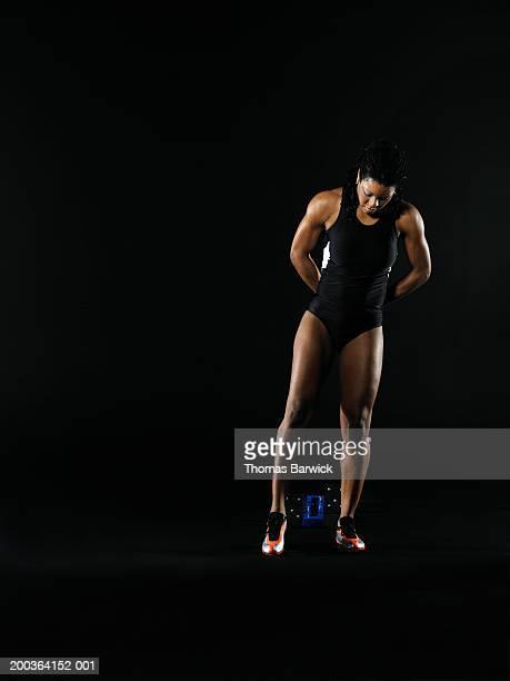 mature female runner stretching beside starting block, looking down - 陸上選手 ストックフォトと画像