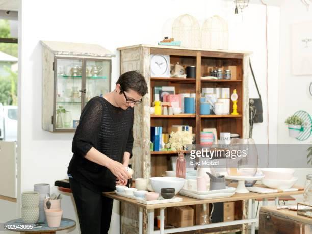 Mature female shop keeper preparing table display in gift shop