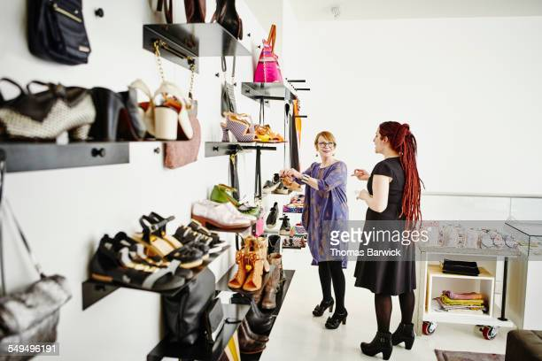 Mature female shop owner showing shoes to customer