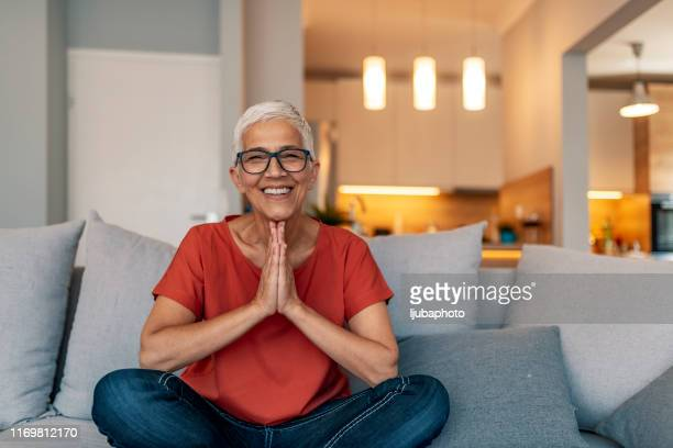 mature female sitting in lotus position doing yoga at home - relief emotion stock pictures, royalty-free photos & images
