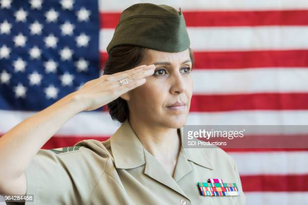 mature female soldier salutes american flag - saluting stock pictures, royalty-free photos & images