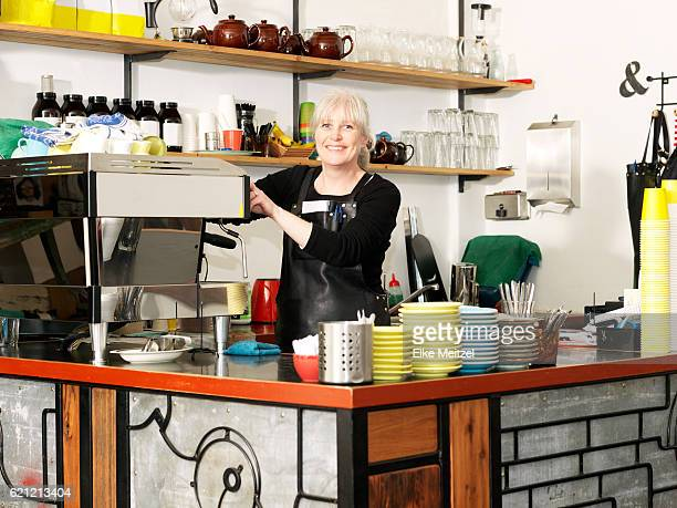 mature female standing by the coffee machine smiling
