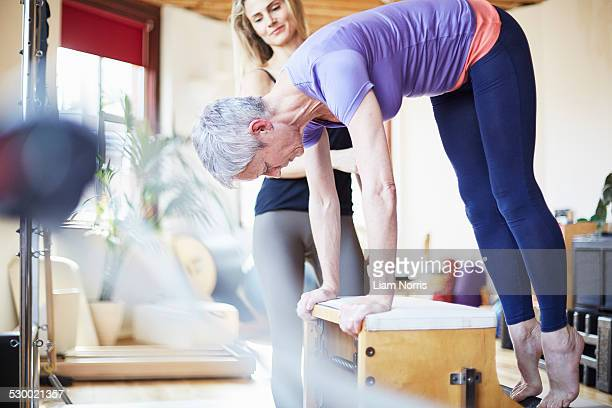 mature female student bending over combo chair in pilates gym - older woman bending over stock pictures, royalty-free photos & images