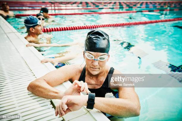 Mature female swimmer checking fitness watch during morning workout in outdoor pool