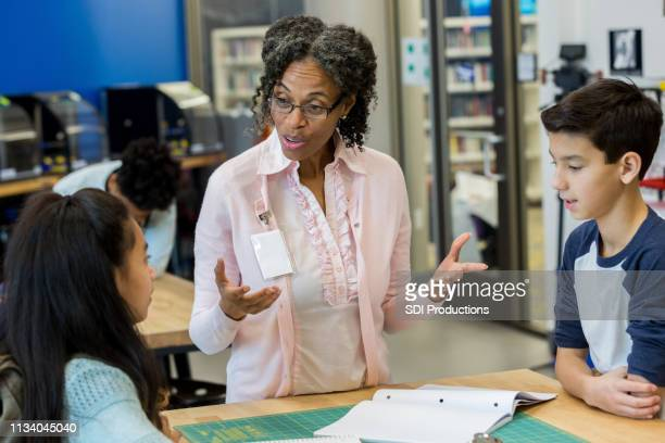 mature female teacher discussing 3d printing project with students - state school stock pictures, royalty-free photos & images