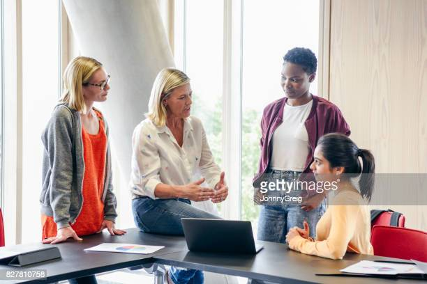 mature female teacher explaining to three female college students - england stock pictures, royalty-free photos & images