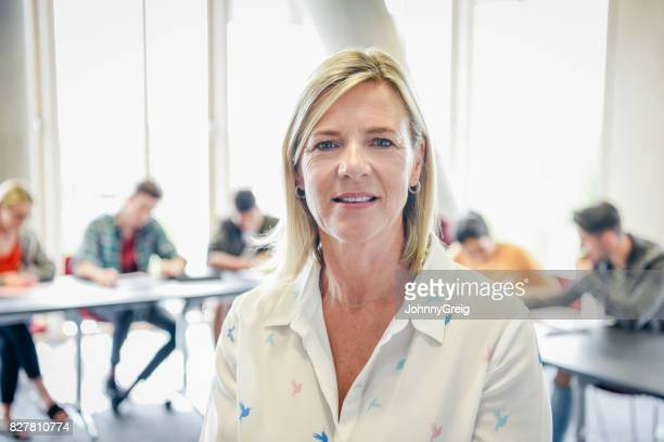Mature female teacher looking at camera, college students working in background