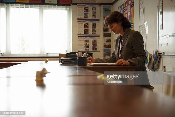 Maduro maestro hembra de marcación de los documentos en el mostrador en montaje tipo aula, lateral