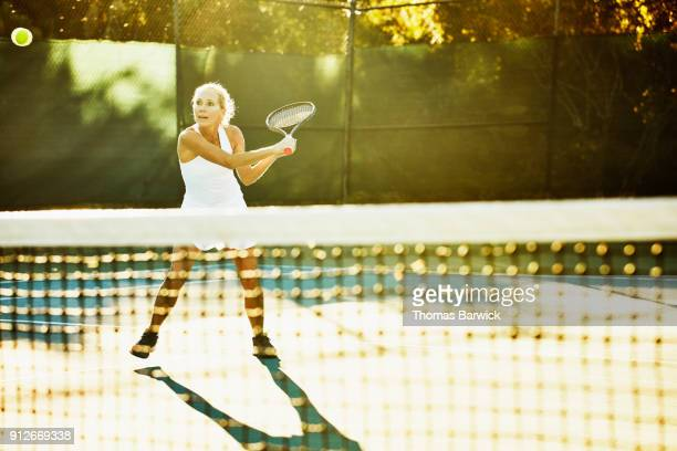 Mature female tennis player hitting backhand return at net during early morning tennis match