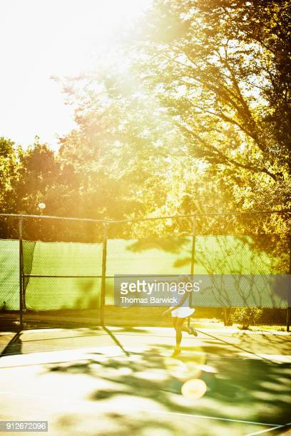 Mature female tennis player hitting serve during early morning tennis match