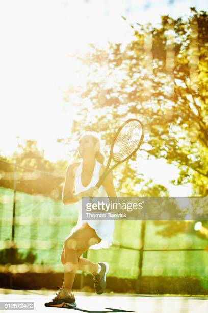 Mature female tennis player hitting shot at net during early morning tennis match