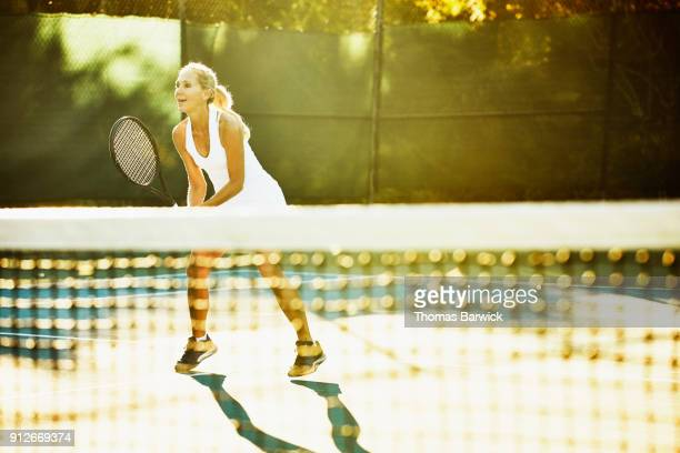 Mature female tennis player playing at net during early morning tennis match