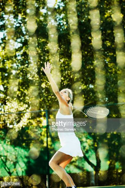 Mature female tennis player practicing overhead shots