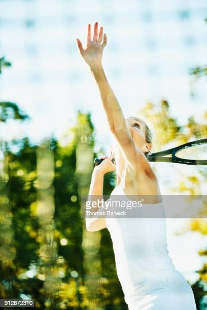 Mature female tennis player preparing to hit overhead shot