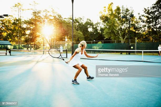 Mature female tennis player preparing to hit return during early morning tennis match