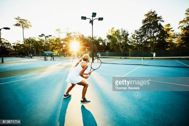 Mature female tennis player preparing to return ball during early morning tennis match
