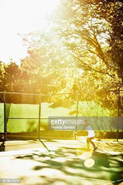 Mature female tennis player preparing to serve during early morning tennis match