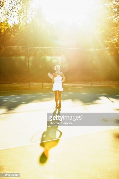 Mature female tennis player walking onto court for early morning tennis workout
