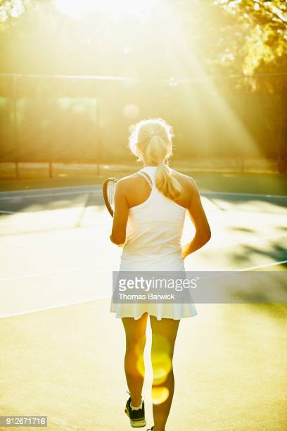 Mature female tennis player walking onto court for early morning tennis match