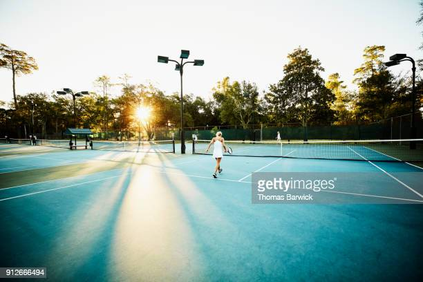 Mature female tennis players picking up balls during early morning tennis match