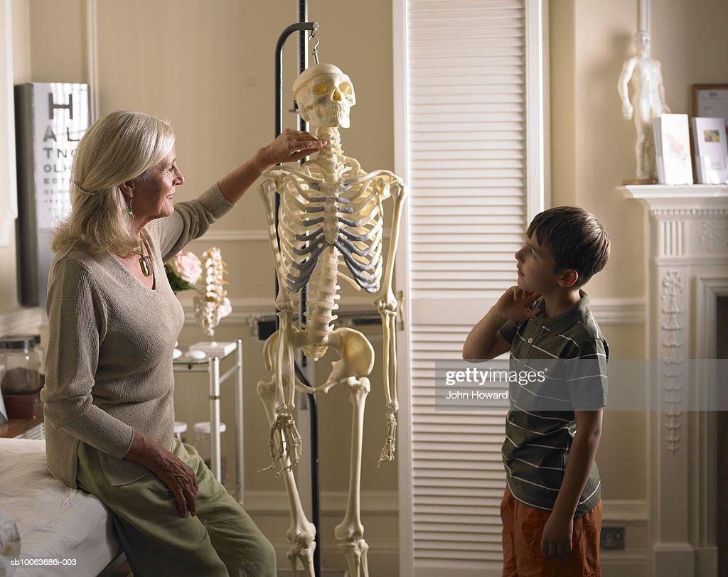 Mature Female Therapist Showing Boy Model Of Human Skeleton Stock