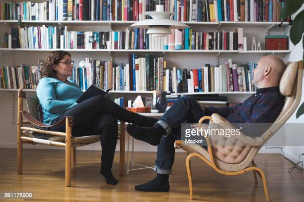 mature female therapist talking to patient by bookshelf at home office - psychiatrist's couch stock pictures, royalty-free photos & images