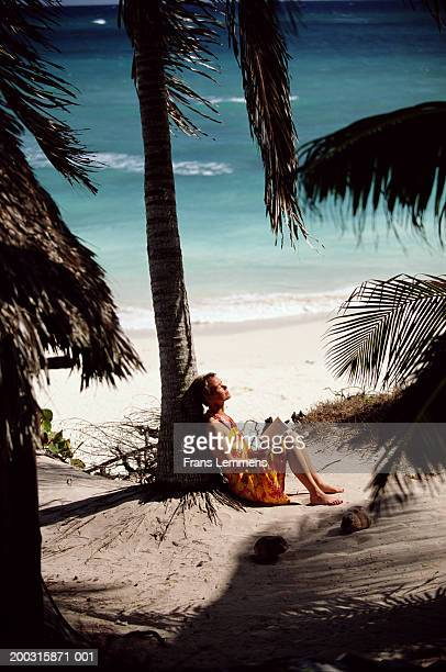 Under the palm tree getty images mature female tourist sitting under palm tree at beach side view voltagebd Image collections