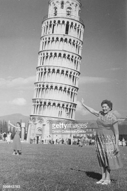 Mature female tourist standing in a field pretending to hold up the Leaning Tower of Pisa a second woman visible in the background also taking a...