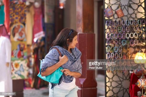 Mature female tourist strolling and looking at market stall, Sharjah, United Arab Emirates