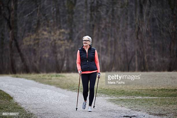 Mature female training in park, nordic walking with poles