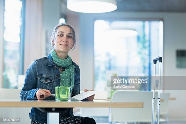 mature female traveller with luggage sitting at table and looking at hotel menu, freiburg im breisgau, baden-w��rttemberg, germany - sigrid gombert stock pictures, royalty-free photos & images
