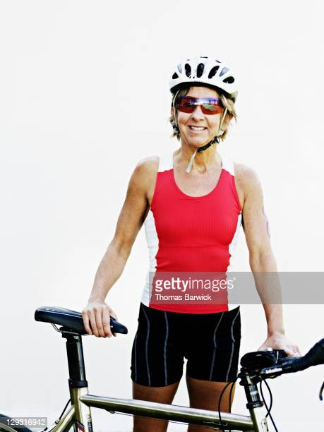 Mature female triathlete standing holding bicycle