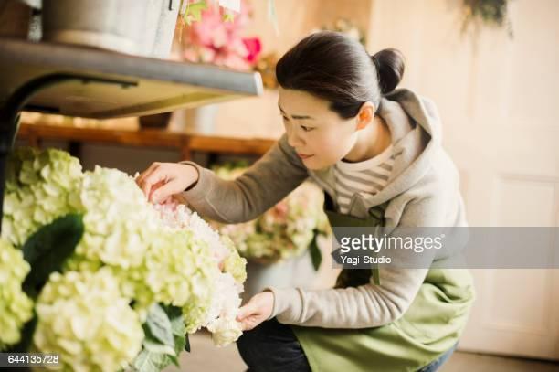 Mature female worker working in flower shop.