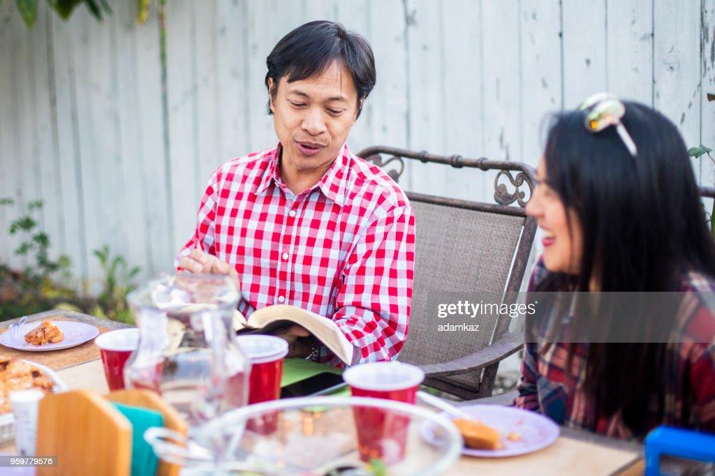 Eine Reife philippinischen Mann liest aus seiner Bibel mit seiner Gruppe : Stock-Foto