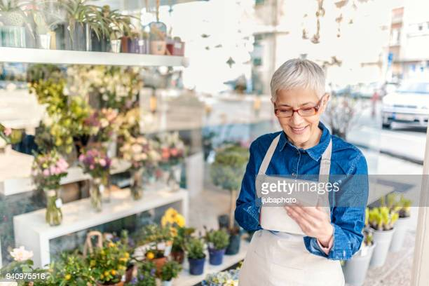 mature florist at work - florist stock pictures, royalty-free photos & images