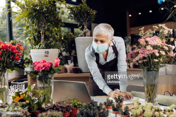 mature florist wearing a face mask and working at her flower store - evento de abertura imagens e fotografias de stock