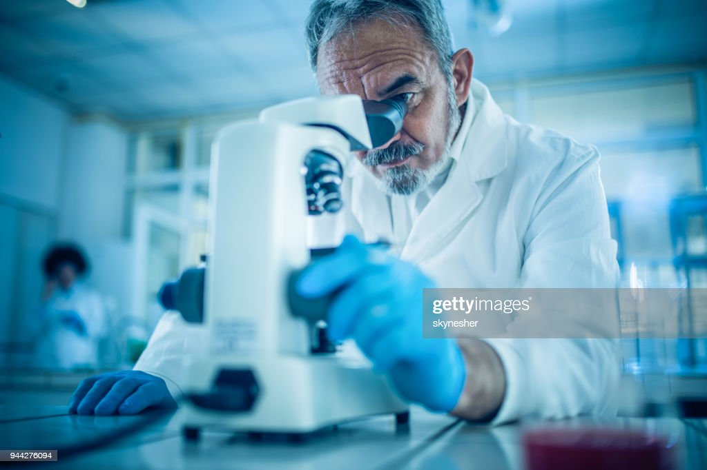 Mature forensic scientist looking through microscope while working on research in a laboratory : Stock Photo