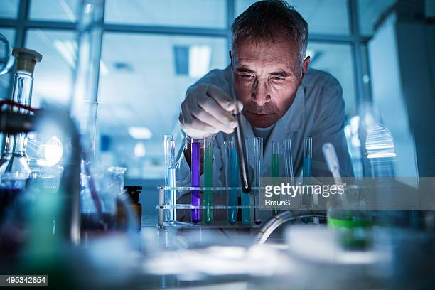 Mature forensic scientist working on test tubes in a laboratory.