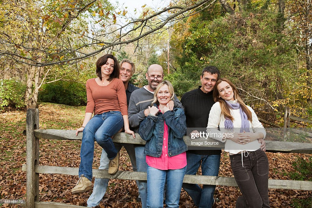 Mature friends around a fence : Stock Photo