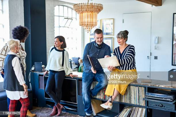 mature friends at social gathering looking at records - music stock pictures, royalty-free photos & images